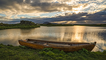 A boat lies in a placid Lake Myvatn, North Iceland at sunset, Iceland