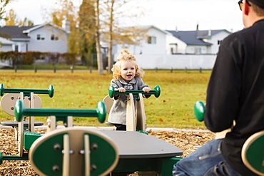 A cute young girl playing on a seesaw with her dad in a playground during the fall season, Spruce Grove, Alberta, Canada
