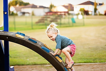 A young girl with blond hair playing in a playground and climbing up a rock ladder on a warm fall day, Spruce Grove, Alberta, Canada