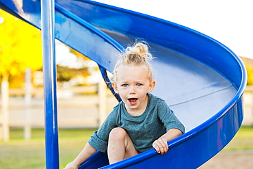 A young girl with blond hair playing in a playground and going down a slide on a warm fall day, Spruce Grove, Alberta, Canada