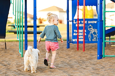 A young girl and her pet dog playing in a playground on a warm fall day, Spruce Grove, Alberta, Canada