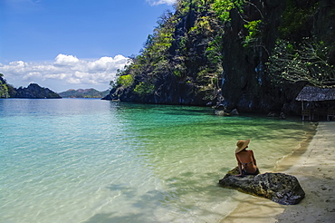 A woman in a bikini sits on a rock along a tropical coastline, Andaman Islands, India