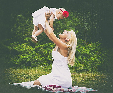 A beautiful young mother with long blonde hair enjoying quality time with her cute baby daughter and tossing her in the air while sitting on the grass in a city park during a summer day, Edmonton, Alberta, Canada