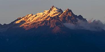 Sunlight illuminating the rugged peaks of the Kangchenjunga Mountain Range, a part of the Great Himalaya Range, Sikkim, India