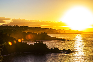 A golden sunset casting yellow light over the ocean and coastline near Honolua Bay, Kaanapali, Maui, Hawaii, United States of America