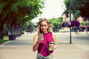 A beautiful young woman walking down a street near a university campus texting on her smart phone, Edmonton, Alberta, Canada - 1116-48424