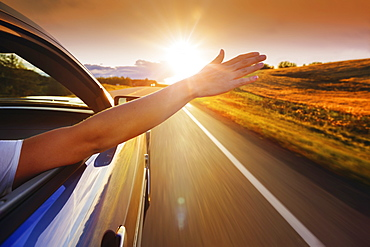 A woman's hand reaches out the window of a vehicle as it travels down the road into the sunset, Edmonton, Alberta, Canada