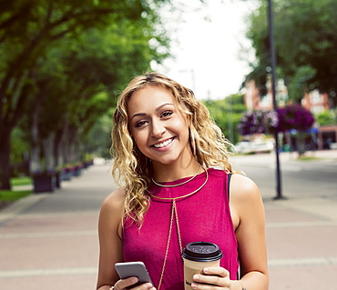 A young woman looks at the camera while walking down a street with a coffee near a university campus and texting on her smart phone, Edmonton, Alberta, Canada