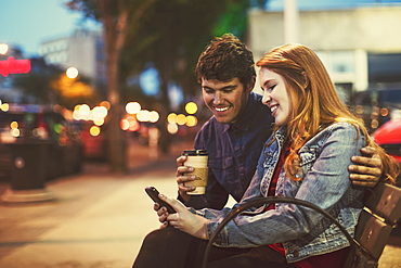 A young couple sits on a bench along a popular street at dusk looking at a smart phone, Edmonton, Alberta, Canada