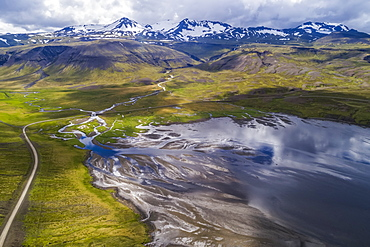 The road winding around Snaefellsness Peninsula with a braided river running into the ocean, Iceland