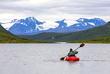 A man paddles a packraft across Landmark Gap Lake with the Alaska Range in the distance, Alaska, United States of America
