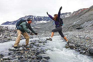 A wife jumps to her husband across an icy stream while hiking near Gulkana Glacier, Alaska, United States of America
