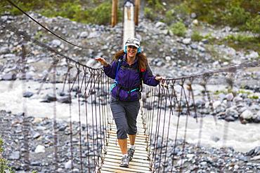 Female hiker crosses a wooden foot bridge on her way to Gulkana Glacier, Alaska, United States of America