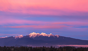 Dramatic glowing clouds above the snow-capped mountains and reflecting on the snow below, British Columbia, Canada