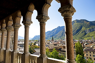 Palace stone columns frames an alpine village in the background with mountains and blue sky, Trento, Trento, Italy