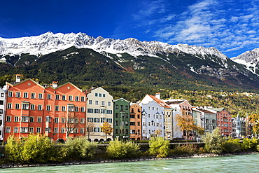 Colourful row of buildings along a riverbank with snow-covered mountain range in the background and blue sky, Innsbruck, Tyrol, Austria