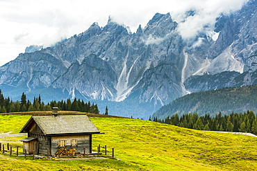 Wooden barn on top of alpine meadow with rugged mountain range in the background, Sesto, Bolzano, Italy