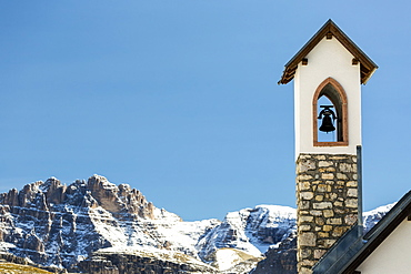 Stone church bell tower with snow-covered mountain range in the background with blue sky, Sesto, Bolzano, Italy