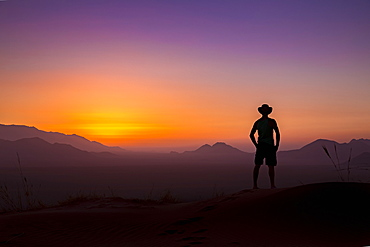 Silhouette of a man wearing a cowboy hat stands looking out at the glowing landscape and sky at sunset, Sossusvlei, Hardap Region, Namibia