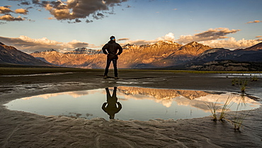 A man stands with his reflection in a pool of water looking out over the Saint Elias Mountains at sunset, Kluane National Park and Reserve, Destruction Bay, Yukon, Canada