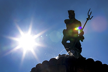 Silhouette of statue on top of fountain with sunburst and blue sky, Trento, Trento, Italy