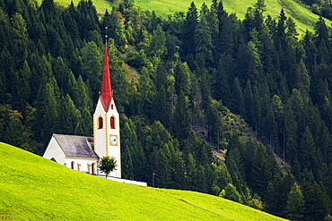 Tall church steeple on grassy alpine slope with treed slope in the background, Parggenhof, Bolzano, Italy
