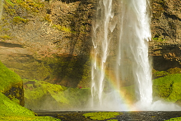 Seljalandsfoss waterfall and a rainbow in the mist, Iceland