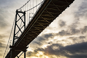 Low angle view of a bridge at sunset with an airplane flying in the distance, Vancouver, British Columbia, Canada