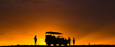Silhouette of tourists on a luxury safari standing beside a recreational vehicle in the desert at sunset, Sossusvlei, Hardap Region, Namibia