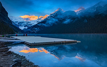 Peaks of the Rocky Mountains illuminated by sunlight and reflected in Lake Louise, Lake Louise, Alberta, Canada