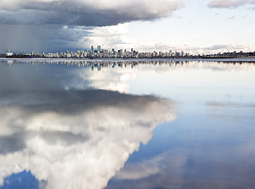 Distant view of the Vancouver skyline over the Pacific Ocean reflecting clouds, viewed from Spanish Banks, Vancouver, British Columbia, Canada