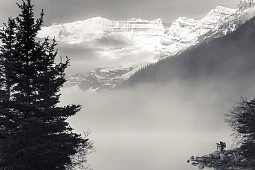 Silhouette of a photographer on the shore of Lake Louise with fog rising from the lake at sunrise, Banff National Park, Lake Louise, Alberta, Canada