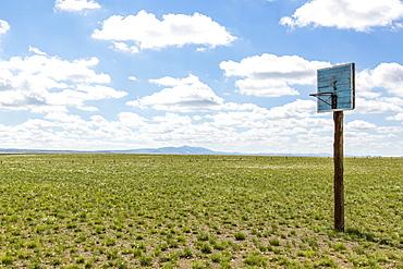 A basketball hoop with backboard in the middle of a grass field in the Gobi desert, Ulaanbaatar, Ulaanbattar, Mongolia