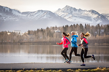 Three young women running on a trail along the water's edge with mountains in the distance, Anchorage, Alaska, United States of America