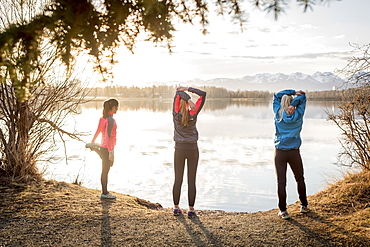 Three young women stretching on a trail at the water's edge, Anchorage, Alaska, United States of America