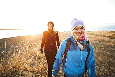 Two young women hiking along the coast at sunrise, Anchorage, Alaska, United States of America