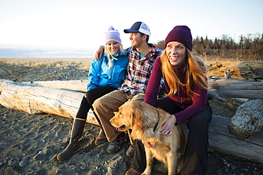 A young couple and a friend with a dog sit on a piece of driftwood on a beach looking out to the ocean at sunset, Anchorage, Alaska, United States of America
