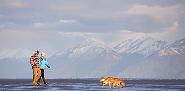 A young couple walking on a beach and holding hands with their dog, and a view of a mountain range in the distance, Anchorage, Alaska, United States of America