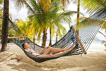 A young woman in a bikini lays in a hammock on a tropical beach with the ocean in the background, Negril, Jamaica