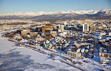 Aerial view of snow covering the sea ice on the frozen shores of downtown Anchorage, the Chugach Mountains in the distance beyond the office buildings and hotels, Cook Inlet in the foreground, South-central Alaska in winter, Anchorage, Alaska, United States of America
