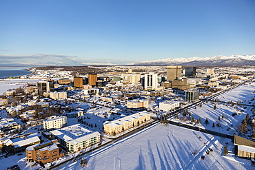 Aerial view of snow covering downtown Anchorage and the Chugach and Talkeetna Mountains stretching out behind the city in the distance, the Park Strip visible in the foreground, South-central Alaska in winter, Anchorage, Alaska, United States of America