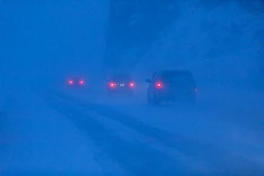Car tail lights illuminate the blowing snow on the Seward Highway during a dark, winter night, Turnagain Arm, Kenai Peninsula, South-central Alaska, Alaska, United States of America