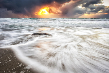 Blur of the tide washing up on the sandy shore along the coast and a golden sun peaking through storm clouds, Nordland, Norway