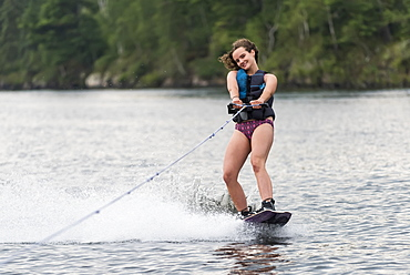 A teenage girl wakeboarding behind a boat on a lake, Lake of the Woods, Ontario, Canada