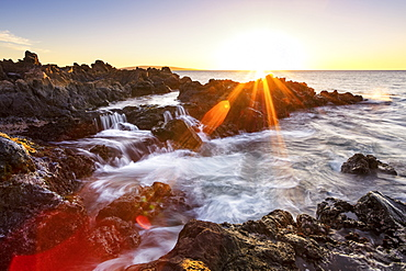 Dramatic sunset over the ocean with waterfalls along the rugged coastline, Wailea, Maui, Hawaii, United States of America