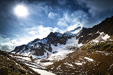 Storm clouds over Aiguille des Glaciers (mountain) and Estellette Glacier and moraine, Alps, Aosta Valley, Italy
