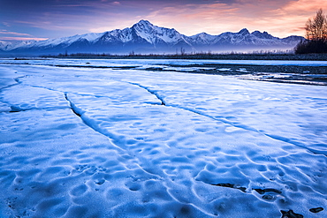 Ice sheet along Matanuska River with a sunset sky and Chugach Mountains in the background, Palmer, Alaska, United States of America