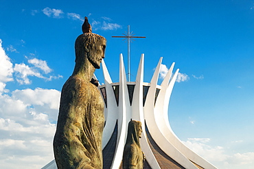 A pigeon sits on the head of an evangelist bronze sculpture outside the Cathedral of Brasilia, Brasilia, Brazil