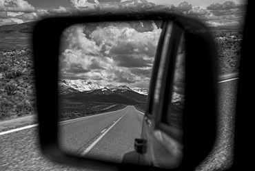 View of the highway and mountains,behind from a vehicle's rear view mirror out the side of the driver's door