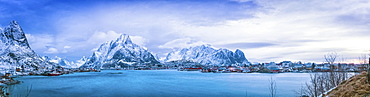 Panoramic of the rugged mountains along the coastline of Norway at sunrise under a blue hue, Svolvar, Lofoten Islands, Nordland, Norway